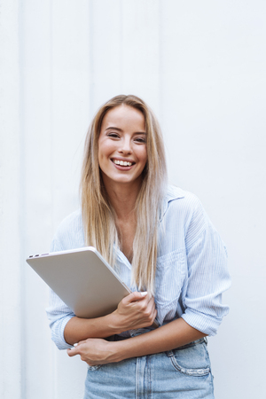Beautiful smiling girl holding laptop computer while standing outdoors Stock fotó