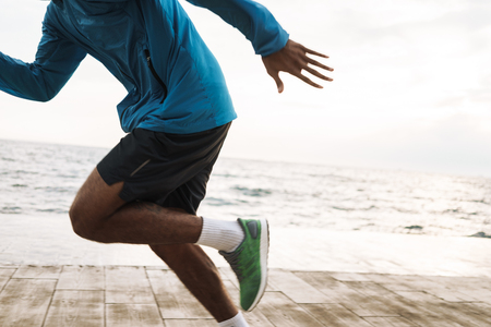 Cropped photo of a strong handsome young african sports man runner outdoors at the beach sea running make exercises.