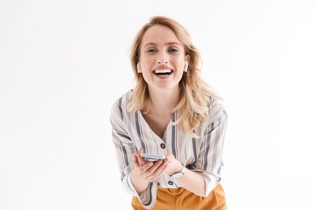 Photo of young smiling woman wearing wrist watch using cellphone and earpods isolated over white background in studio 写真素材