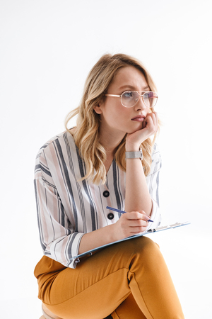 Photo of european thinking woman wearing glasses sitting in chair and looking aside isolated over white background in studio Banco de Imagens