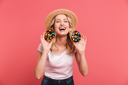 Portrait of curly blond woman 20s wearing straw hat laughing while holding tasty sweet donuts isolated over pink background