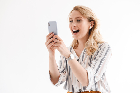 Photo of young joyful woman wearing wrist watch using cellphone and earpod isolated over white background in studio
