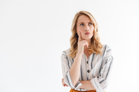 Portrait of beautiful blond woman 20s wearing casual clothes thinking and looking aside at copyspace isolated over white background in studio Banco de Imagens