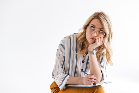 Photo of blond serious woman wearing glasses propping her head and looking upward while sitting in chair isolated over white background in studio Banco de Imagens - 123328944