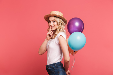 Portrait of trendy blond woman 20s wearing straw hat smiling while holding bunch of colorful balloons isolated over pink background Stock Photo