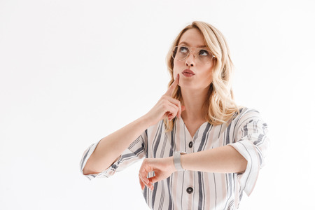 Portrait of beautiful serious woman wearing wristwatch thinking and looking upward at copyspace isolated over white background in studio Banco de Imagens