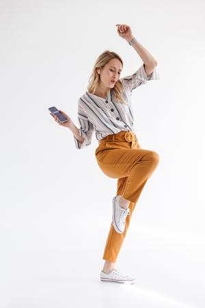 Foto de cuerpo entero de una mujer europea bailando y sosteniendo el teléfono móvil mientras escucha música a través de un auricular aislado sobre fondo blanco.