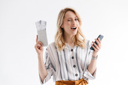 Portrait of blond young woman wearing casual clothes using cellphone while holding traveling tickets and passport isolated over white background in studio