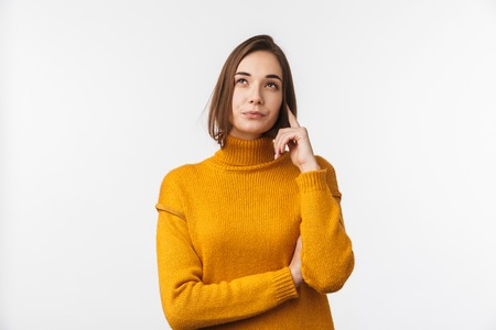 Portrait of a pensive beautiful young woman wearing sweater standing isolated over white background 免版税图像
