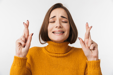 Portrait of a beautiful young woman wearing sweater standing isolated over white background, holding fingers crossed for good luck