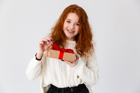 Image of a beautiful young cute girl redhead posing isolated over white wall background holding gift box.