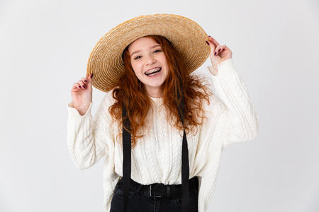 Image of a beautiful young cute girl redhead posing isolated over white wall background wearing hat. Banque d'images