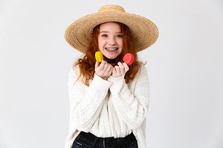 白い背景の上に孤立した夏の帽子をかぶった陽気な若い10代の少女の肖像画を閉じ、マカロンを持つ