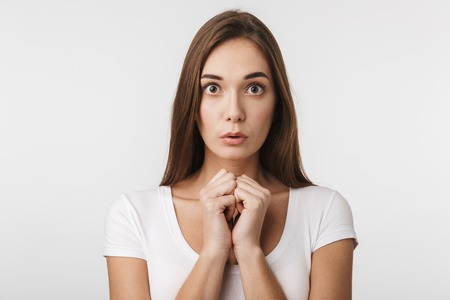 Portrait of a beautiful confused young woman wearing casual clothing standing isolated over white background