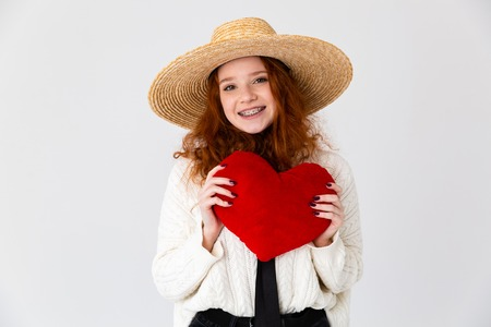 Image of a beautiful young cute girl redhead posing isolated over white wall background holding heart toy.