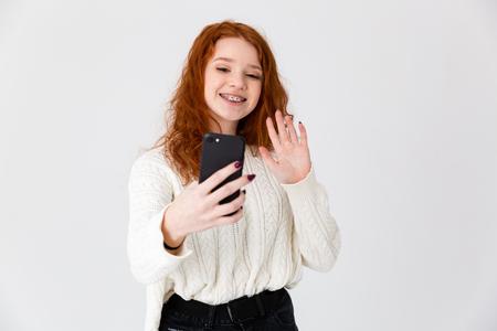 Image d'une belle jeune fille rousse posant isolée sur fond de mur blanc prendre un selfie.