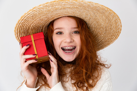 Close up portrait of a cheerful young teenage girl wearing summer hat standing isolated over white background, showing present box