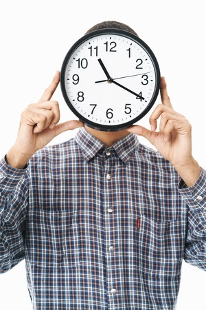 Portrait of a happy young man wearing plaid shirt standing isolated over white background, cover face with wall clock Banque d'images - 123847038