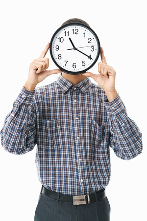 Portrait of a happy young man wearing plaid shirt standing isolated over white background, cover face with wall clock Banque d'images - 123847042
