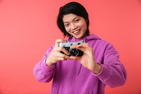 Portrait of a cheerful asian man standing isolated over pink background, taking a picture with photo camera