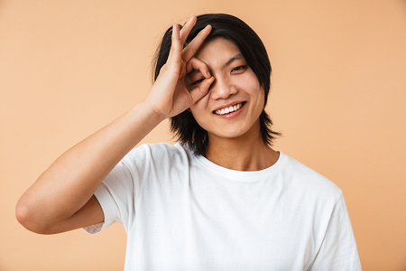 Portrait of a happy asian man wearing t-shirt standing isolated over beige background, showing ok