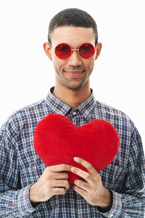 Portrait of a happy young man wearing plaid shirt standing isolated over white background, holding red heart