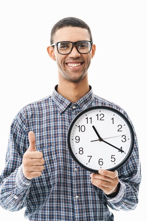 Portrait of a happy young man wearing plaid shirt standing isolated over white background, showing wall clock, thumbs up Banque d'images - 123847154