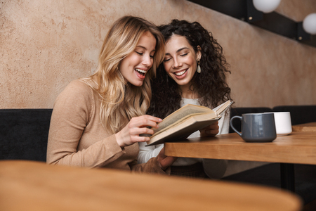 Image of excited happy pretty girls friends sitting in cafe drinking coffee reading book. Stock Photo