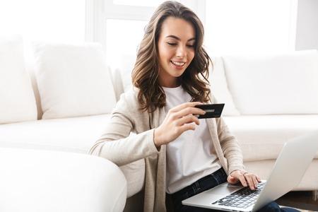 Schöne junge Frau, die am Laptop arbeitet, während sie im Wohnzimmer sitzt und Kreditkarte zeigt