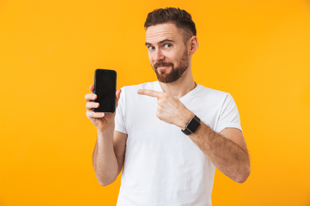 Image of young happy man posing isolated over yellow wall background showing display of mobile phone.