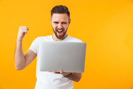 Image of young excited man posing isolated over yellow wall background using laptop computer. 스톡 콘텐츠 - 124365152