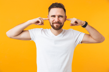 Image of young handsome man posing isolated over yellow wall background covering ears. Stock Photo