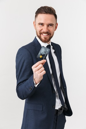 Image of happy young businessman posing isolated over white wall background holding credit card.