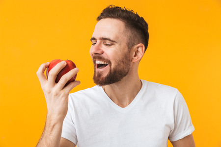 Photo of a happy young handsome man posing isolated over yellow wall background holding apple.