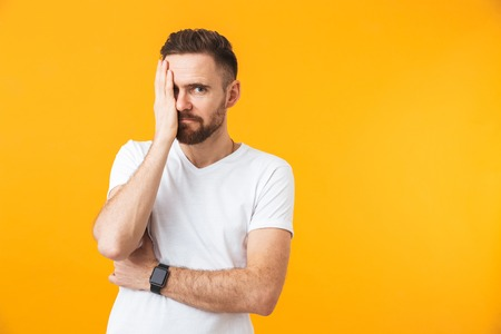 Image of young man posing isolated over yellow wall background covering eye.