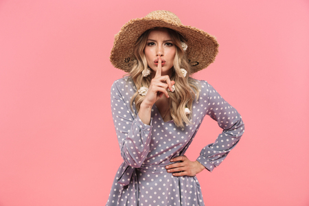 Portrait of a beautiful young blonde woman wearing summer straw hat standing isolated over pink background, showing silence gesture
