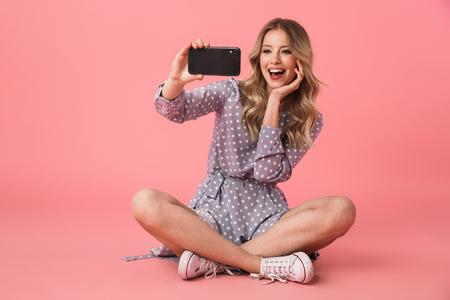 Porträt eines fröhlichen jungen blonden Mädchens, das auf einem Boden sitzt, isoliert über rosafarbenem Hintergrund, und macht ein Selfie
