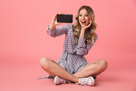 Portrait of a cheerful young blonde girl sitting on a floor isolated over pink background, taking a selfie
