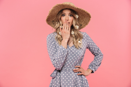 Portrait of a shocked beautiful young blonde woman wearing summer straw hat standing isolated over pink background, covers mouth Stock Photo