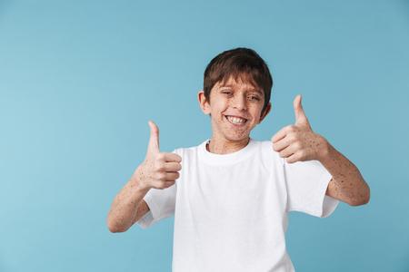 Gros plan Portrait d'un beau garçon heureux de 10 à 12 ans avec des taches de rousseur portant un t-shirt décontracté blanc souriant et montrant les pouces vers le haut isolé sur bleu Banque d'images