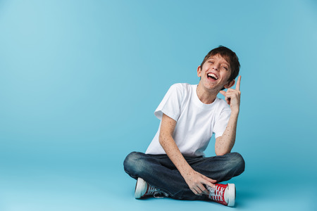 Image of thin brunette boy 10-12y with freckles wearing white casual t-shirt showing finger upward while sitting on floor isolated over blue