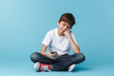 Image d'un garçon européen attrayant de 10 à 12 ans avec des taches de rousseur portant un t-shirt décontracté blanc tenant et utilisant un smartphone assis sur le sol isolé sur bleu Banque d'images