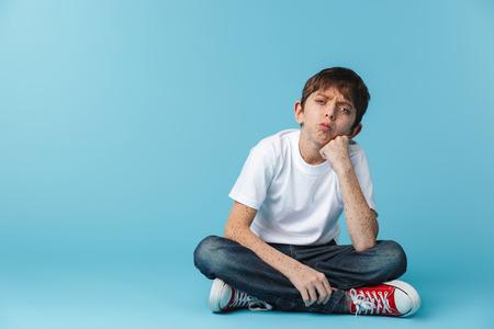 Image d'un garçon brun caucasien de 10 à 12 ans avec des taches de rousseur portant un t-shirt décontracté blanc regardant la caméra alors qu'il était assis sur le sol isolé sur bleu