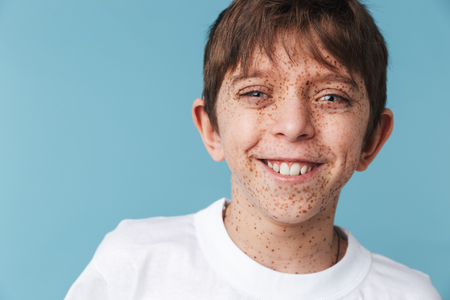 Portrait closeup of beautiful youngster boy 10-12y with freckles wearing white casual t-shirt smiling at camera isolated over blue Stockfoto