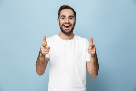 Cheerful excited man wearing blank t-shirt standing isolated over blue
