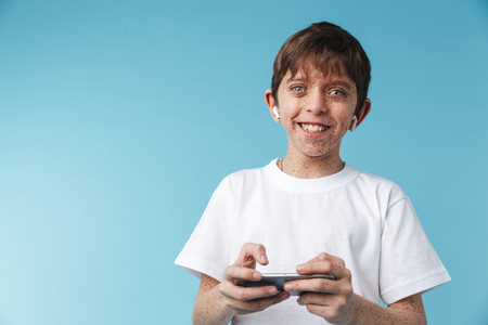 Image of happy caucasian boy 10-12y with freckles wearing white casual t-shirt smiling and holding smartphone isolated over blue