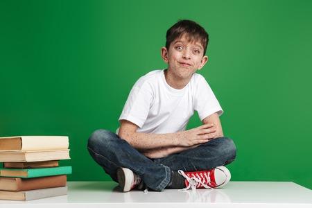 Joli petit garçon joyeux avec des taches de rousseur étudiant, assis avec une pile de livres sur le vert