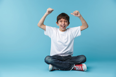Image of happy brunette boy 10-12y with freckles wearing white casual t-shirt smiling at camera while sitting on floor isolated over blue