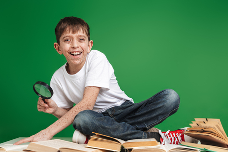 Cute cheerful little boy with freckles studying, sitting with stack of books over green
