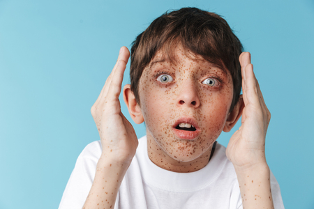 Image closeup of shocked caucasian boy 10-12y with freckles wearing white casual t-shirt looking at camera isolated over blue